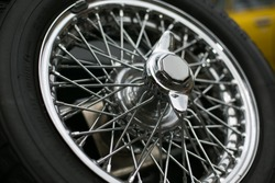 The highly contrasting tyre rubber and polished chrome of a vintage car wheel