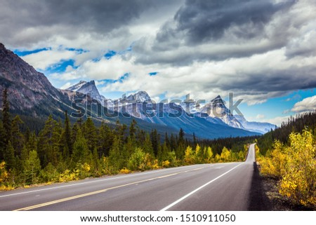 The highway crosses the Rocky Mountains of Canada. Magnificent northern autumn. Canadian Rockies. The concept of active, automotive, environmental and photo tourism #1510911050