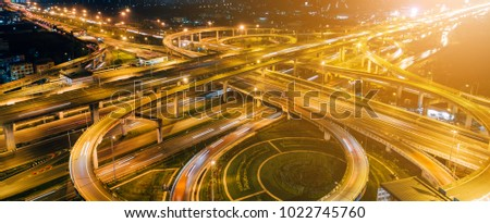 The highway in the big city, expressway enter the city, night light picture by drone on top view.