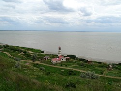 The hills are covered with green grass. In the background is a lighthouse by the sea.
