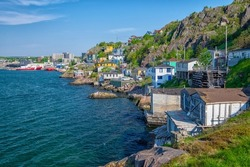 The hillside of St. John's Harbour, Newfoundland, on a sunny day, under blue sky and white clouds. The colorful wooden houses are scattered along the hillside with the blue ocean in the foreground.