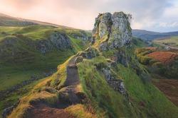 The hilltop tourist attraction Castle Ewan at the Fairy Glen in golden sunset or sunrise light on the Isle of Skye, Scotland.