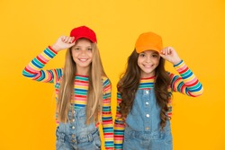 The hipster subculture. Happy little hipsters wearing baseball caps on yellow background. Cute small hipsters smiling with fashionable look. Adorable children in hipster style.