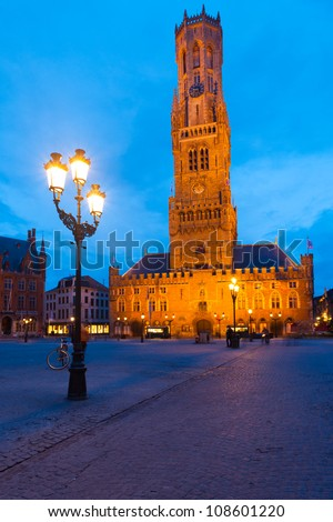 The historic belfry and city center square with street lamps in the old medieval old town of Bruges (Brugge), Belgium at blue hour
