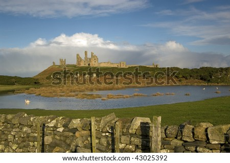 The historic Dunstanburgh castle as seen over a stone wall