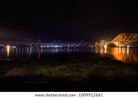 The historic Victorian Red Forth Road rail bridge on the right with the newer Forth Road road crossings on the left, taken late at night at low tide.