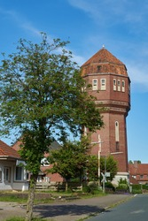 the historic watertower in Nordenham (district Wesermarsch, Germany) seen behind a blooming tree on a sunny summer day