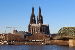 The Hohenzollern bridge over Rhine river on a sunny day. The Cologne Cathedral (Kolner Dom) in the city of Cologne, Germany. It is the largest Gothic church in northern Europe.