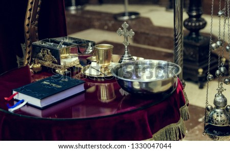 The Holy Bible, holy water and cross on church table, prepared for Chistening ceremony #1330047044