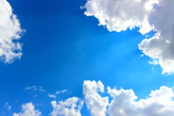 The Holy Light comes from heaven. Sunlight pass through white cumulus clouds with bright blue sky. Clouds is lit from behind by the sun's rays. Natural background with copy space.