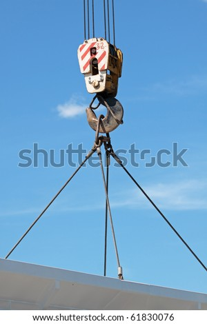 The hook of the elevating crane lifts a concrete plate against the blue sky, a close up
