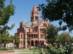 The Hopkins County Courthouse framed by trees. It is a historic building designed with Romanesque revival architectural style in Sulphur Springs, Texas.