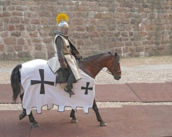 The horse knight in an armor, going on a horse along a stone wall
