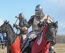 The horse knight in an armour and in a helmet with a sword in a hand