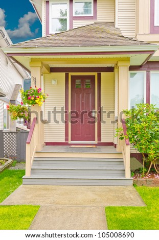 The house entrance with the red colored door