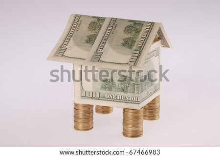 The house from dollars costs on coins. Flood Insurance. On grey background.