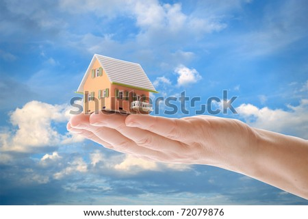 The house in human hands of the blue sky with clouds - stock photo