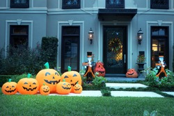 The house is decorated for Halloween:Many different pumpkins with faces and two dead man butlers with signs in their hands. Night, Houston, Texas, United States