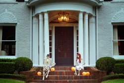 The house is decorated for Halloween: Two skeletons with orange pumpkins sitting near the entrance to the house. Evening