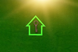 The house is green, with an old iron key lock on a green background. The concept of home protection, property ownership.