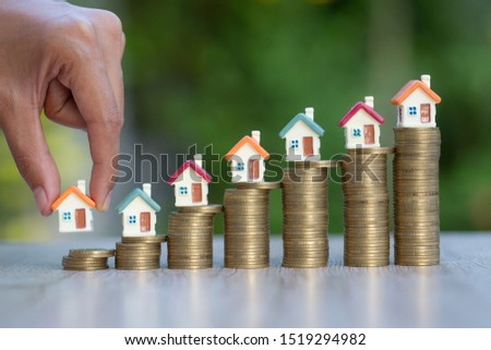 The house on the coin hand ladder is about to put the house on the coin, real estate concepts, mortgages and investments, save money or invest for future houses, areas to enter text.