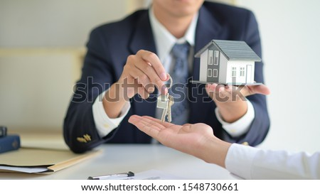 The house selling broker holds the keys and the model house is given to the customers,Real estate concept. Foto stock ©
