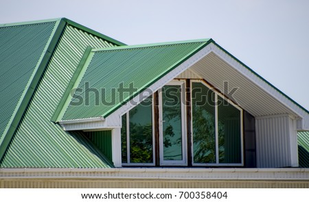The house with plastic windows and a green roof of corrugated sheet. Roofing of metal profile wavy shape on the house with plastic windows. Green roof of corrugated metal profile and plastic windows.