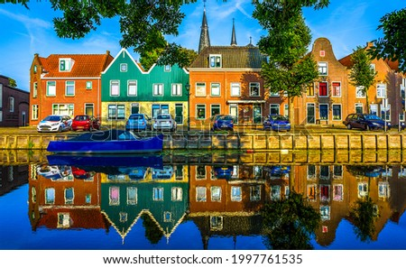 The houses are reflected in the river water. Town houses reflection in river. River town houses view