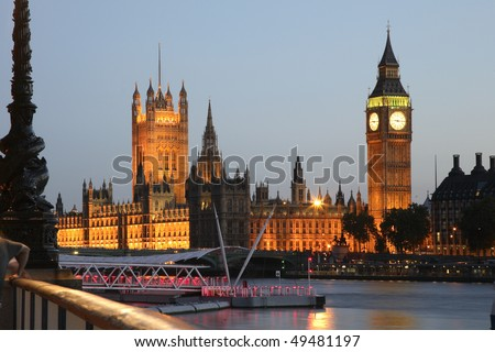 The Houses of Parliament at Westminster Palace in London, seen from across the Thames River at dusk. Horizontal shot.