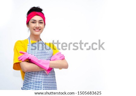 The housewife wears yellow clothes, wears an apron, wears pink gloves, stands for the index finger and makes stressful faces. Copy area