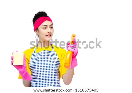 The housewife wears yellow clothes, wears an apron, wears pink gloves, stands for the index finger and makes stressful faces. Copy space.