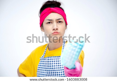 The housewife wears yellow clothes, wears an apron, wears pink gloves, stands for the index finger and makes stressful faces. Copy area.
