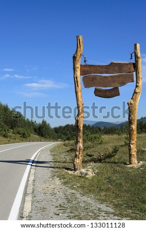 The huge blank wooden sign by the highway. Clear skies and sunny day on the hills.