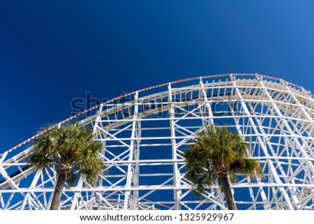 The huge curving climb of old fashioned white wooden roller coaster tracks contrasts against a brilliant blue sky and two palm trees. #1325929967