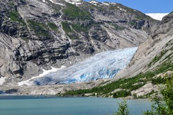 The huge Jostedalsbreen glacier in the middle of the rocky mountains above a lake in Norway