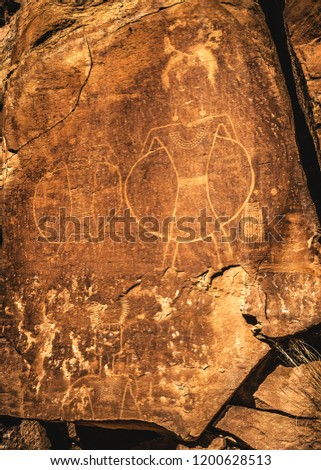 """The """"hula hoop"""" anthropomorph petroglyphs at Mcconckie Ranch in Dry Fork Canyon near Vernal, Utah, USA. This unique rock art seems to depict warriors (or possible ancient aliens) in a halo or shield. #1200628513"""