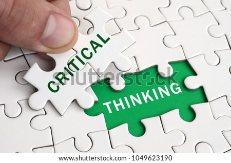 The human hand fills the last missing elements of the surface from the jigsaw puzzle. Image with words critical and thinking