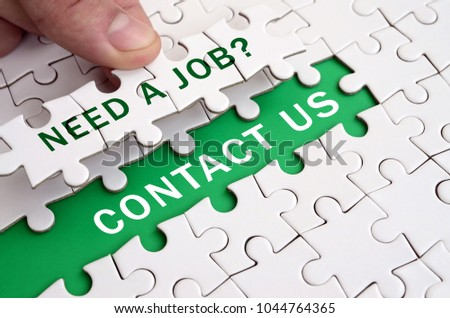 Stock Photo The human hand fills the last missing elements of the surface from the jigsaw puzzle. Need a job. Contact us