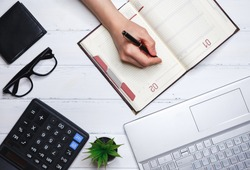 The human hand writes down plans for current affairs, training, implementation and business development in the daily diary.Concept of planning and successful business management