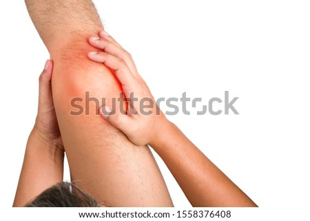 The human hands touching on the knee having pain from muscle strain, He touches the red dot with painful and suffers on isolated white background with clipping path.