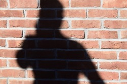 The human shadow on a brick wall isolated unique stock photograph