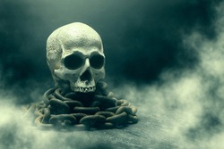 The human skull on the chains close-up. Death. Smoke blanketing. Mystical symbol. Abstract dark blue background. Easy image tinting.