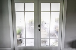 The humidity of the outdoor temperature on a summer day in South Georgia. The air conditioning is on inside and the cold air inside makes the back glass pane doors condensate and become foggy.