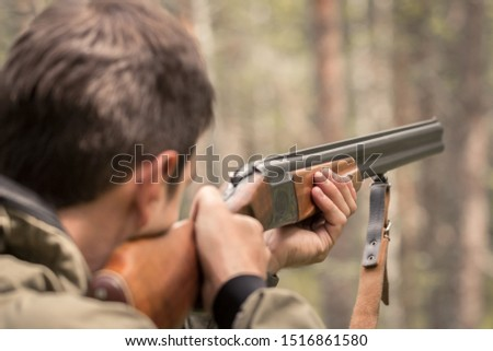 The hunter takes aim and is ready to shoot from a double barreled shotgun. Huntsman in the forest waiting for prey. Targeted rifle in the hands of a poacher.  #1516861580