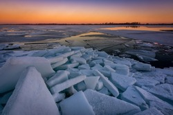 The ice on the river gathered in a heap. Winter sunset on the background of ice.