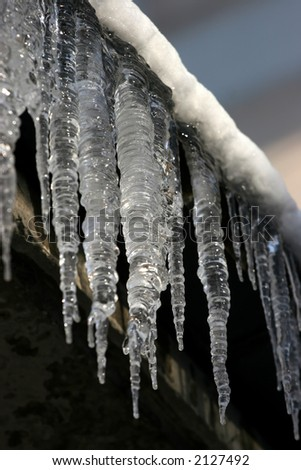 The icicles which are hanging down from a roof at home