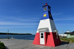 The iconic Chetiicamp Harbour Lighthouise painted in the design of the Acadian flag on the Cabot Trail in Cape Breton, Nova Scotia, Canada