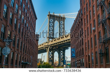 The Iconic Manhattan Bridge Viewed From Dumbo, Brooklyn, between two brick buildings with the Empire State building framed in the bottom (New York, September 2017). #733638436