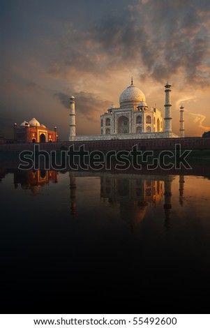The iconic Taj Mahal and sunset sky beautifully reflected in the calmly flowing Jamuna river. - stock photo