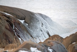 The icy shore of Hudson Bay, northern Manitoba, Churchill in Canada. Sea ice snow and freezing water up against the side of a rock on the beach shoreline.